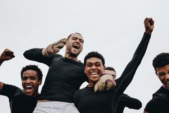 Low angle view of players carrying their teammate on shoulders celebrating success. Group of happy soccer players celebrating a stock photos