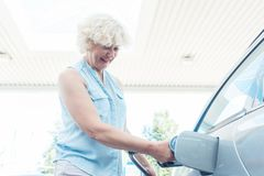 Active senior woman smiling while filling up the gas tank of her Stock Image