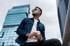 Young man wearing blue denim jacket while daydreaming outdoors i. Low angle view portrait of a young man wearing sunglasses and blue denim jacket while Stock Image