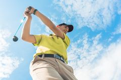 Low-angle view of a professional player holding the club during individual game. Low-angle view of a professional player wearing golf outfits while holding the royalty free stock photos