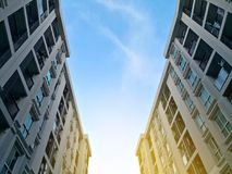 Low angle view of residential building condominium or apartment. With blue sky and cloud and sun shine flare background stock images