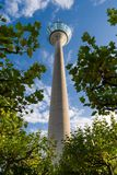 Low-angle view of the Rhine Tower in Dusseldorf against a cloudy blue sky Stock Photos