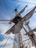 Old Tall Ship Sail, Mast, and Riggings Against Blue Sky royalty free stock images