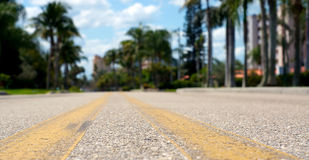 Low angle view of road. Ground level view of road between yellow lines, shallow depth of field Stock Photography