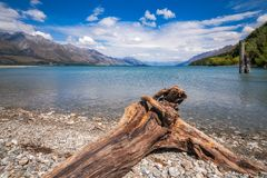 Low angle view from the rocky Dart river banks at Kinloch, NZ. Low angle View from the rocky Dart river bed at Kinloch with mountain range and wooden piers in Stock Photography