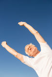 Low angle view of senior man exercising against blue sky Stock Images