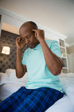 Low angle view of senior man suffering from headache at home. Low angle view of senior man suffering from headache while sitting on bed at home Royalty Free Stock Images