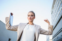 Low angle view of serious classy businesswoman making victory ge. Sture outdoors on urban background royalty free stock photo