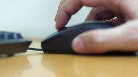 Low angle view from the side of a man working on a. Computer mouse stock footage