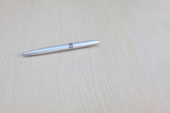 Low angle view of a silver pen on a wood desktop Royalty Free Stock Image