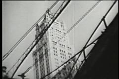 Low angle view of skyscraper behind elevated subway, 1930s stock video footage