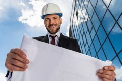 Low angle view of smiling bearded architect holding blueprint and looking royalty free stock image