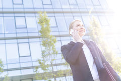 Low angle view of smiling businesswoman using cell phone on sunny day Royalty Free Stock Photo