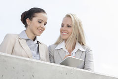 Low angle view of smiling businesswomen using digital tablet while standing on terrace against sky Royalty Free Stock Photos