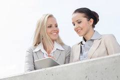 Low angle view of smiling businesswomen using digital tablet while standing on terrace against sky Royalty Free Stock Images