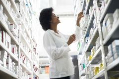 Smiling Female Chemist Arranging Stock In Shelves At Pharmacy. Low angle view of smiling female chemist arranging stock in shelves at pharmacy stock photos