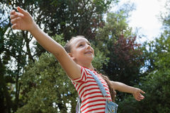Low angle view of smiling girl with arms outstretched standing against trees Stock Images