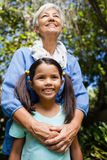 Low angle view of smiling grandmother and granddaughter standing against trees. At backyard Royalty Free Stock Photography