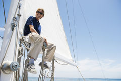 Low angle view of smiling man sitting on yacht boom. Low angle view of smiling men sitting on yacht boom Stock Photo