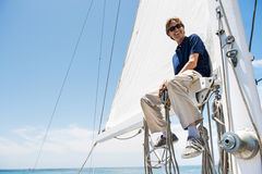 Low angle view of smiling man sitting on yacht boom Stock Photos