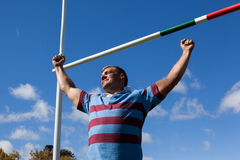 Low angle view of smiling rugby player with arms raised against blue sky. Low angle view of smiling rugby player with arms raised by goal post against blue sky Royalty Free Stock Photography