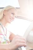 Low angle view of smiling woman driving car Royalty Free Stock Photo