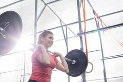 Low angle view of smiling woman lifting barbell in crossfit gym Stock Photos