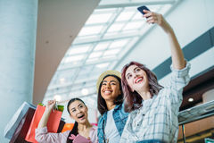 Low angle view of smiling young women with shopping bags taking selfie. Young girls shopping concept Stock Photos