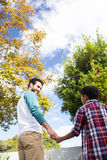 Low angle view of son and father holding hands. While standing against tree in yard Royalty Free Stock Image