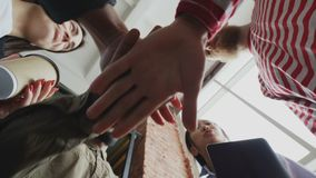 Low angle view of start-up business team of multi-ethnic people put palms together after successful agreement about new. Low angle view of start-up business team stock video footage