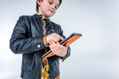 Low angle view of stylish boy using tablet. On grey Royalty Free Stock Photography
