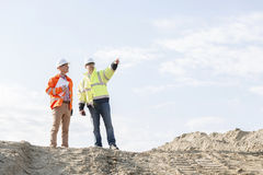Low angle view of supervisor showing something to colleague at construction site Royalty Free Stock Photos