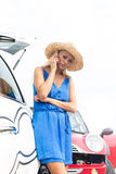 Low angle view of tensed woman using cell phone by broken down cars Royalty Free Stock Photography