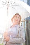 Low angle view of thoughtful businesswoman holding umbrella outdoors royalty free stock photo