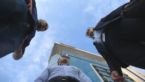 Low angle view of three business men standing outdoor near office and talking. Businessmen meet and speaking outside in. The city with blue sky at background stock video footage