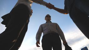 Low angle view of three business men standing outdoor near office and talking. Businessmen meet and speaking outside in. The city with blue sky at background stock footage