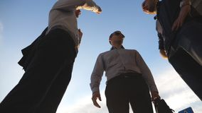 Low angle view of three business men standing outdoor and talking. Businessmen meet and speaking outside in city with. Blue sky at background. Communication of stock video footage