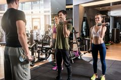 Three young people smiling while alternating dumbbell bicep curl Royalty Free Stock Image