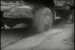 Low-angle view trucks driving through muddy road stock video