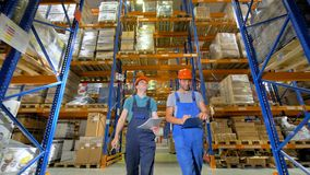 Low angle view on two men overseeing a warehouse condition. stock video footage