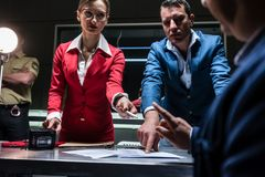 Two persuasive investigators trying to obtain a confession from. Low-angle view of two persuasive investigators trying to obtain a signed confession from a Royalty Free Stock Photo