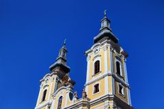 Low-angle view of towers of sunlit Baroque church in Hungary stock photography
