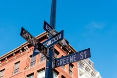 Typical building and street name sign in New York. Low angle view of typical building and street name sign in Greene Street and Spring Street in Soho District in royalty free stock photos