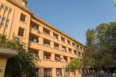 Facade of apartment and dormitory sun drying hanging clothes lin. Low angle view of university dorm with sun drying hanging clothes line in dense of apartments Stock Images