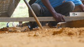 Low angle view of unrecognizable indian male hands checking levels for accuracy during building wooden floor. Local. Builders working on construction area stock video
