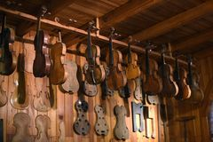 Violins hanging in luthier workshop royalty free stock images