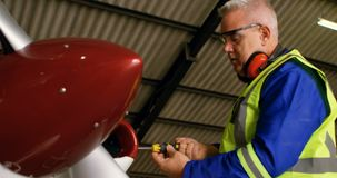 Engineer repairing aircraft at aerospace hangar 4k
