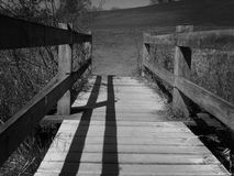 Low angle view of a walkway bridge over water. In black and white Royalty Free Stock Photos