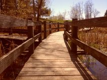 Low angle view of a walkway bridge over water. Warm view of a wooden walk bridge in pond or lake Stock Images