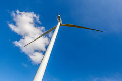 Low angle view of wind turbine against cloudy blue sky in wind f Stock Images